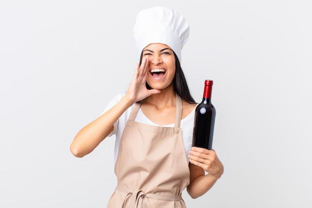 Mooie spaanse chef-kokvrouw die zich gelukkig voelt, een grote schreeuw geeft met de handen naast de mond en een fles wijn vasthoudt