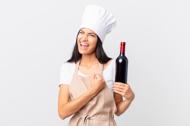 Mooie spaanse chef-kokvrouw die zich gelukkig voelt en een uitdaging aangaat of viert en een fles wijn vasthoudt
