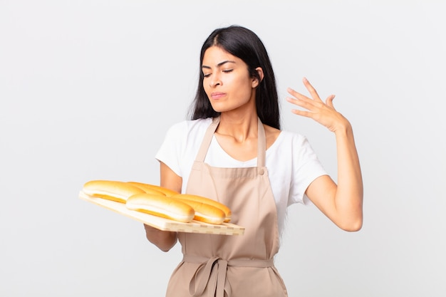 Mooie spaanse chef-kokvrouw die zich gestrest, angstig, moe en gefrustreerd voelt en een dienblad met broodbroodjes vasthoudt
