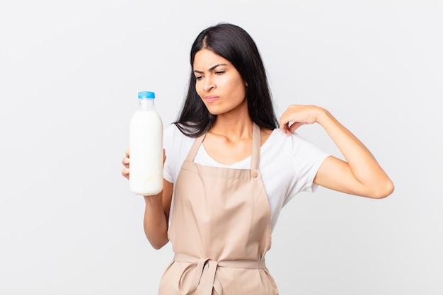 Mooie spaanse chef-kokvrouw die zich gestrest, angstig, moe en gefrustreerd voelt en een melkfles vasthoudt