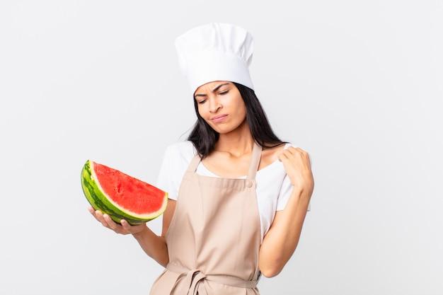 Mooie spaanse chef-kokvrouw die zich gestrest, angstig, moe en gefrustreerd voelt en een watermeloen vasthoudt