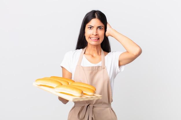 Mooie spaanse chef-kokvrouw die zich gestrest, angstig of bang voelt, met de handen op het hoofd en een dienblad met broodbroodjes vasthoudt