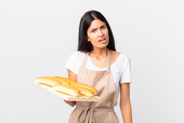 Mooie spaanse chef-kokvrouw die zich verbaasd en verward voelt en een dienblad met broodbroodjes vasthoudt