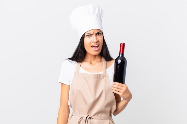 Mooie spaanse chef-kokvrouw die zich verbaasd en verward voelt en een fles wijn vasthoudt