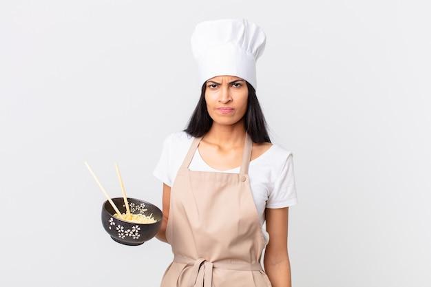 Mooie spaanse chef-kokvrouw die zich verdrietig, overstuur of boos voelt en opzij kijkt en een noedelkom vasthoudt
