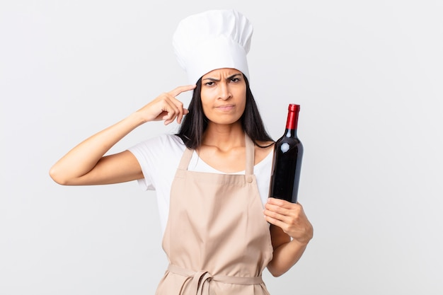 Mooie spaanse chef-kokvrouw die zich verward en verbaasd voelt, laat zien dat je gek bent en een fles wijn vasthoudt