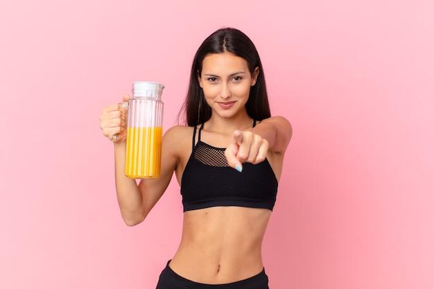 Mooie spaanse fitnessvrouw met een sinaasappelsap