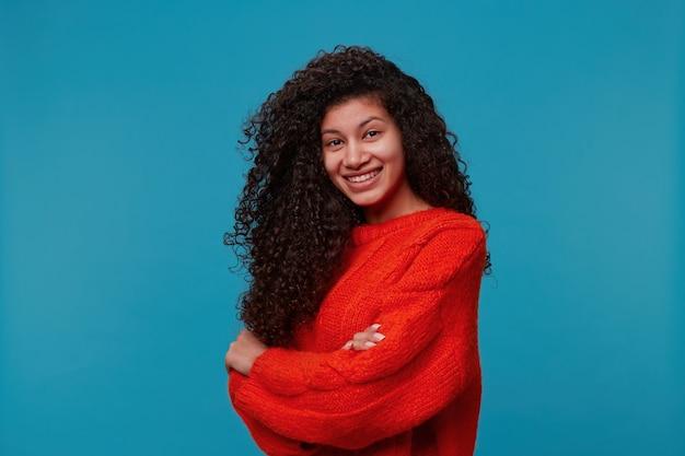 Mooie spaanse latino vrouw staat halve draai met gekruiste armen kijkt gelukkig en glimlacht