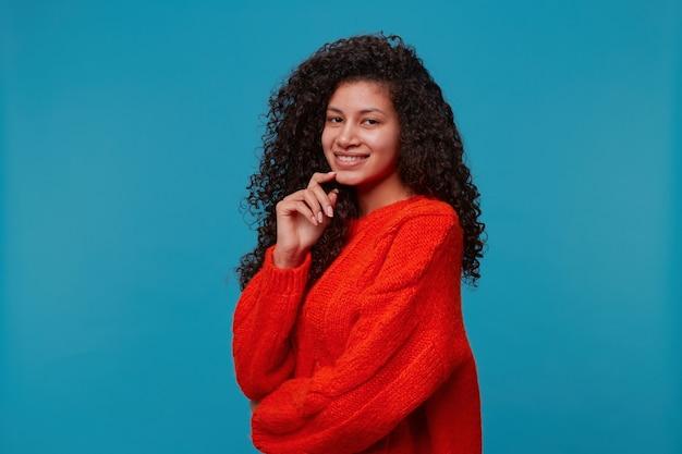 Mooie spaanse latino vrouw staat halve draai met hand aanraken gezicht kijkt blij en glimlacht