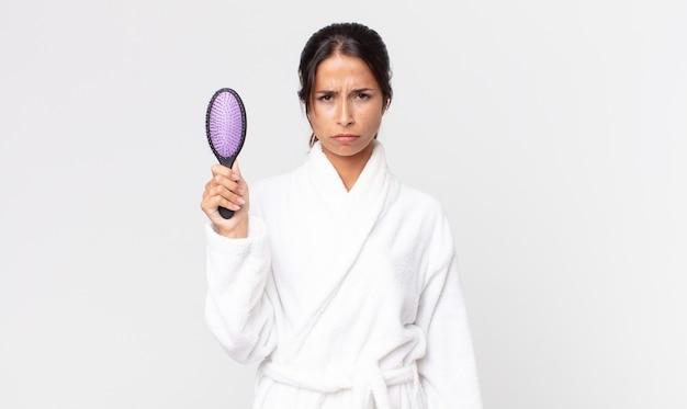 Mooie spaanse vrouw die een badjas draagt en een haarborstel vasthoudt