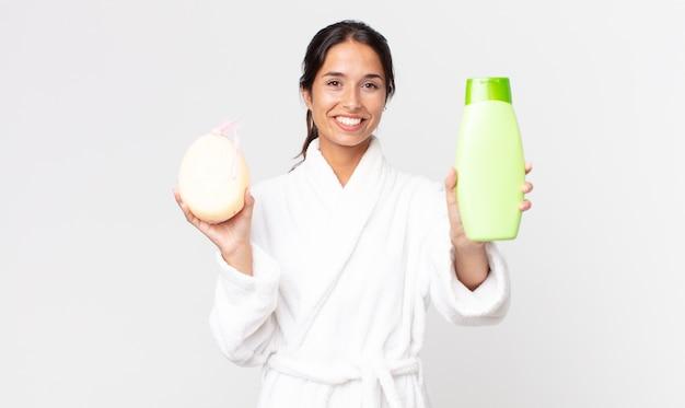 Mooie spaanse vrouw die een badjas draagt en een shampoo en een spons vasthoudt
