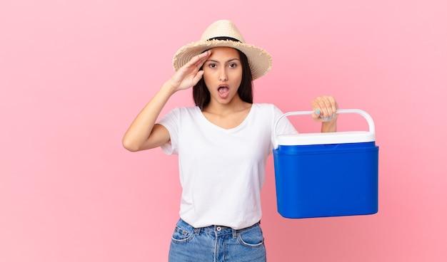 Mooie spaanse vrouw die er blij, verbaasd en verrast uitziet en een draagbare koelkast vasthoudt