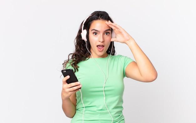 Mooie spaanse vrouw die er blij, verbaasd en verrast uitziet met een koptelefoon en een smartphone