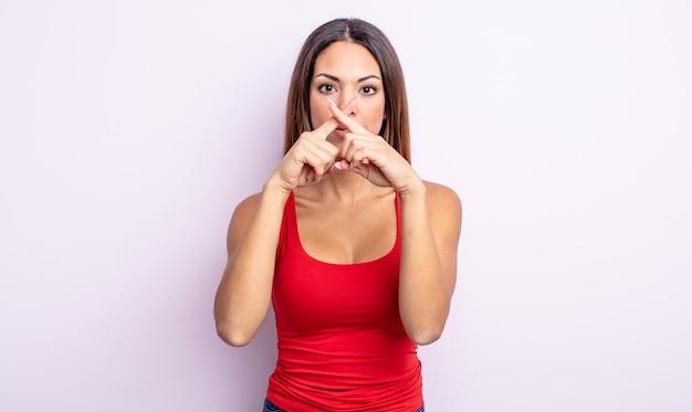 Mooie spaanse vrouw die er serieus uitziet en ontevreden is met beide vingers vooraan gekruist in afwijzing, en vraagt om stilte