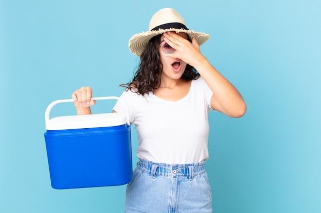 Mooie spaanse vrouw die geschokt, bang of doodsbang kijkt, haar gezicht bedekt met een hand die een draagbare koelkast vasthoudt
