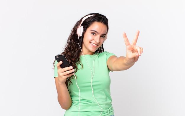 Mooie spaanse vrouw die lacht en er gelukkig uitziet, gebarend naar overwinning of vrede met een koptelefoon en een smartphone