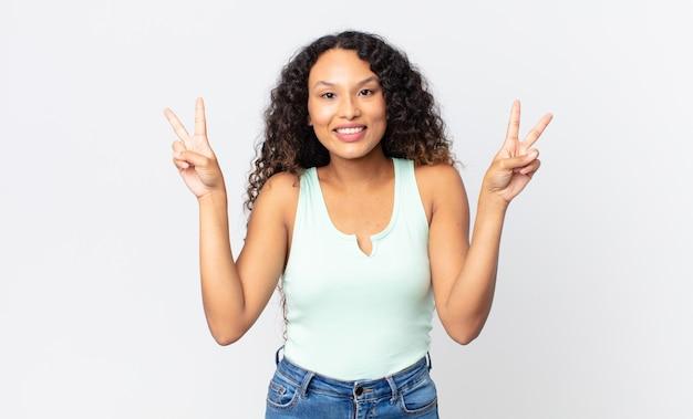 Mooie spaanse vrouw die lacht en er gelukkig, vriendelijk en tevreden uitziet, gebarend overwinning of vrede met beide handen