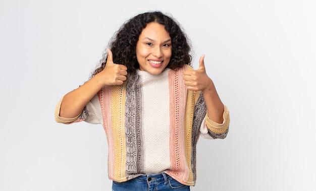 Mooie spaanse vrouw die lacht en er in het algemeen gelukkig, positief, zelfverzekerd en succesvol uitziet, met beide duimen omhoog