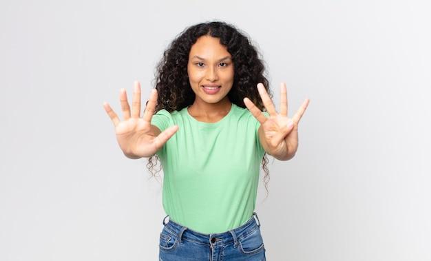 Mooie spaanse vrouw die lacht en er vriendelijk uitziet, nummer negen of negende toont met de hand naar voren, aftellend
