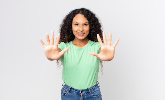 Mooie spaanse vrouw die lacht en er vriendelijk uitziet, nummer tien of tiende toont met de hand naar voren, aftellend