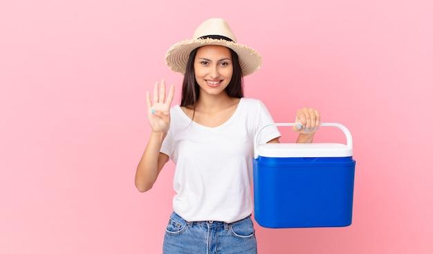 Mooie spaanse vrouw die lacht en er vriendelijk uitziet, nummer vier toont en een draagbare koelkast vasthoudt