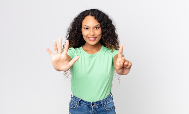 Mooie spaanse vrouw die lacht en er vriendelijk uitziet, nummer zes of zesde toont met de hand naar voren, aftellend