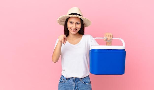Mooie spaanse vrouw die naar de camera wijst en jou kiest en een draagbare koelkast vasthoudt