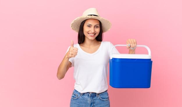 Mooie spaanse vrouw die trots is, positief glimlacht met duimen omhoog en een draagbare koelkast vasthoudt