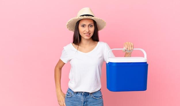Mooie spaanse vrouw die verbaasd en verward kijkt en een draagbare koelkast vasthoudt