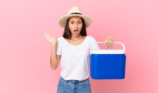 Mooie spaanse vrouw die verrast en geschokt kijkt, met open mond terwijl ze een voorwerp vasthoudt en een draagbare koelkast vasthoudt