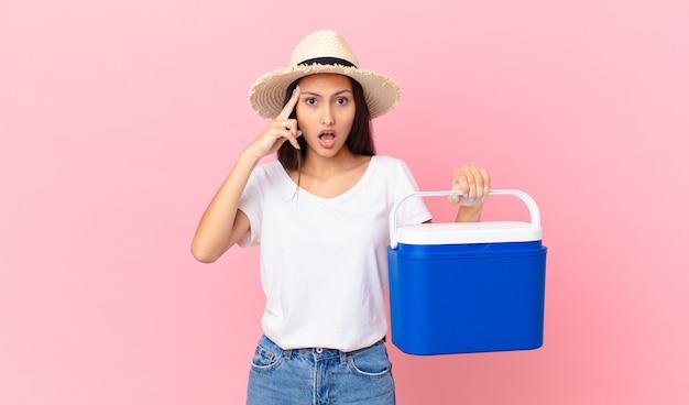 Mooie spaanse vrouw die verrast kijkt, een nieuwe gedachte, idee of concept realiseert en een draagbare koelkast vasthoudt