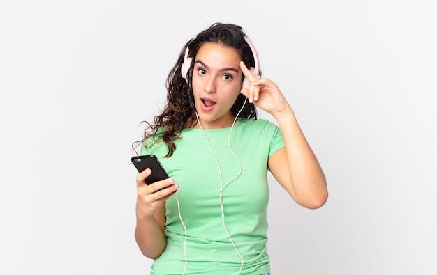 Mooie spaanse vrouw die verrast kijkt en een nieuwe gedachte, idee of concept realiseert met een koptelefoon en een smartphone