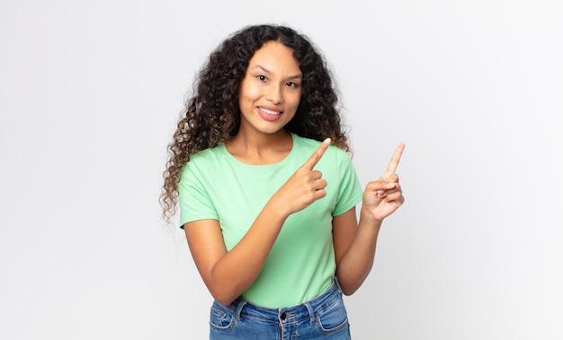 Mooie spaanse vrouw die vrolijk lacht en naar de zijkant en naar boven wijst met beide handen die een object in de kopieerruimte tonen
