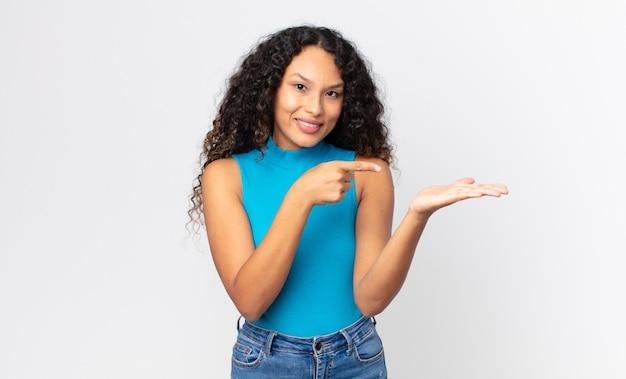 Mooie spaanse vrouw die vrolijk lacht en wijst om de ruimte op de handpalm aan de zijkant te kopiëren, een object te tonen of te adverteren
