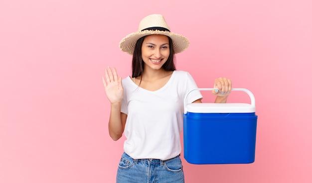 Mooie spaanse vrouw die vrolijk lacht, met de hand zwaait, je verwelkomt en begroet en een draagbare koelkast vasthoudt