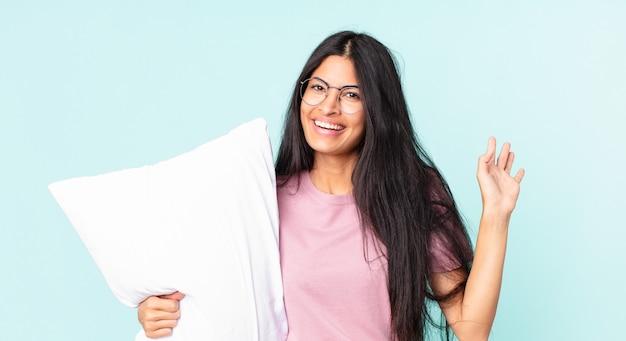 Mooie spaanse vrouw die vrolijk lacht, met de hand zwaait, je verwelkomt en begroet en een pyjama draagt met een kussen