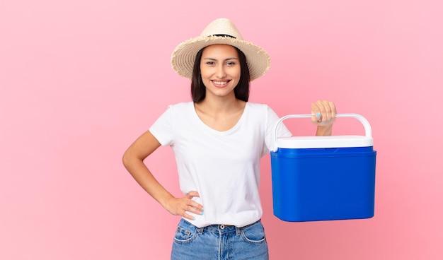 Mooie spaanse vrouw die vrolijk lacht met een hand op de heup en zelfverzekerd en een draagbare koelkast vasthoudt