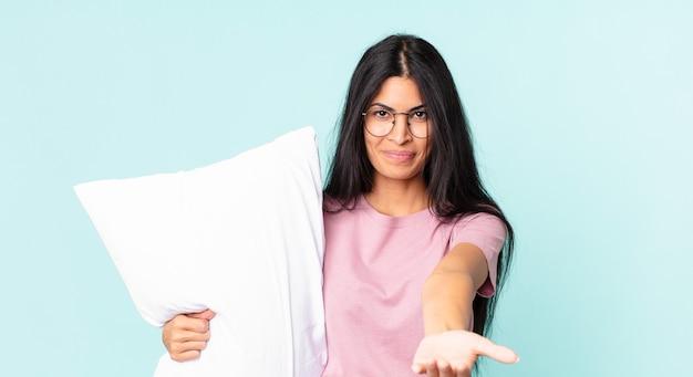 Mooie spaanse vrouw die vrolijk lacht met vriendelijk en een concept aanbiedt en toont en een pyjama draagt met een kussen
