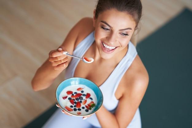 Mooie spaanse vrouw die yoghurt eet die een gezonde levensstijl en een dieet promoot