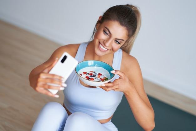 Mooie spaanse vrouw die yoghurt eet en een smartphone vasthoudt die een gezonde levensstijl en een dieet promoot