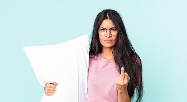 Mooie spaanse vrouw die zich boos, geïrriteerd, opstandig en agressief voelt en een pyjama draagt met een kussen