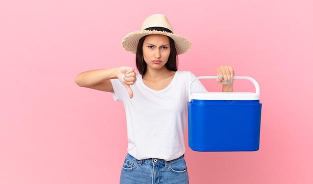 Mooie spaanse vrouw die zich boos voelt, duimen naar beneden laat zien en een draagbare koelkast vasthoudt