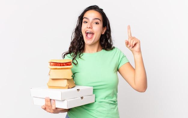 Mooie spaanse vrouw die zich een gelukkig en opgewonden genie voelt na het realiseren van een idee en het vasthouden van afhaalmaaltijden voor fastfood