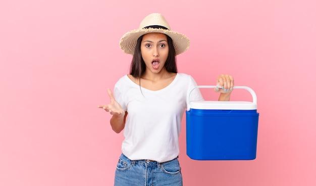 Mooie spaanse vrouw die zich extreem geschokt en verrast voelt en een draagbare koelkast vasthoudt