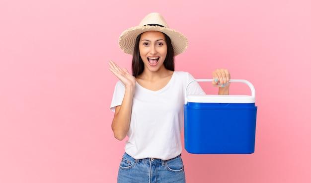 Mooie spaanse vrouw die zich gelukkig en verbaasd voelt over iets ongelooflijks en een draagbare koelkast vasthoudt