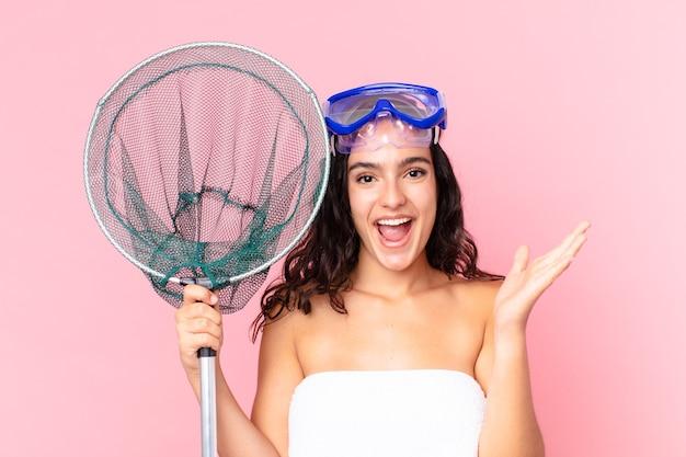 Mooie spaanse vrouw die zich gelukkig en verbaasd voelt over iets ongelooflijks met een veiligheidsbril en een visnet