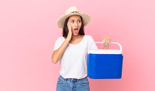 Mooie spaanse vrouw die zich gelukkig, opgewonden en verrast voelt en een draagbare koelkast vasthoudt