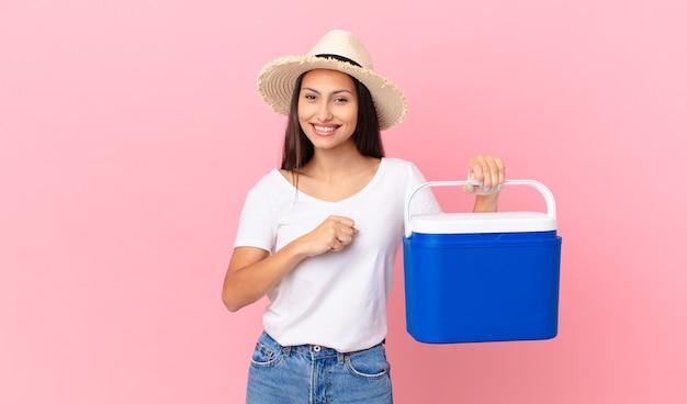 Mooie spaanse vrouw die zich gelukkig voelt en een uitdaging aangaat of een draagbare koelkast viert en vasthoudt