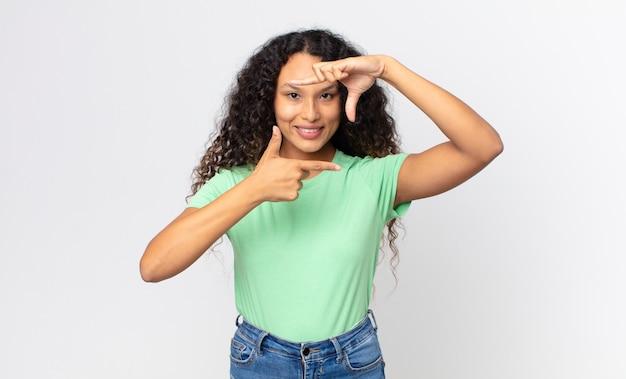 Mooie spaanse vrouw die zich gelukkig, vriendelijk en positief voelt, lacht en een portret of fotolijst maakt met handen