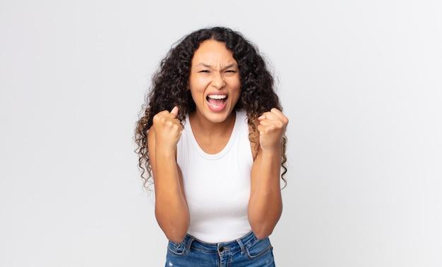 Mooie spaanse vrouw die zich geschokt, opgewonden en gelukkig voelt, lacht en succes viert, en zegt wow! Premium Foto